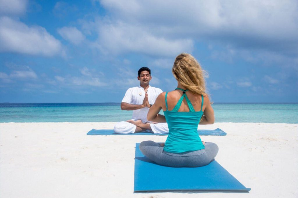 Realeaxing yoga on the beach at Finolhu