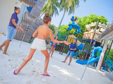 Childrens are play volleyball with the supervisors