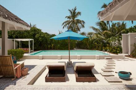 Von Palmen umgebene Terasse mit privatem Pool, Sonnenliegen und Strandzugang