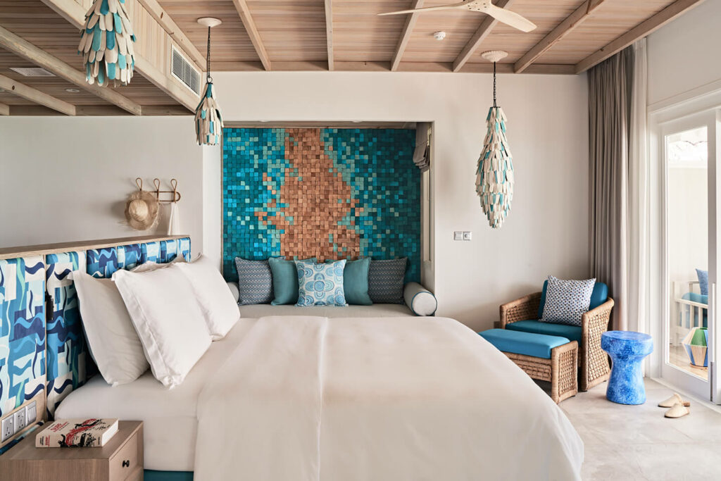 Luxurious bedroom in lagoon villa with king size bed and turquoise and wooden decoelements