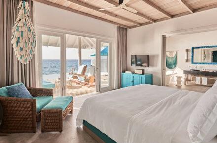 Lujosa habitación de la Ocean Pool Villa con detalles en color turquesa y vista al mar